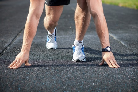tenseness: Start. Close up of male legs. The athlete is kneeing before running on the road Stock Photo