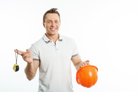 manual measuring instrument: Handsome male worker is holding orange helmet and tape-measure in his hands. He is smiling and looking at the camera with joy. Isolated on background and copy space in right side