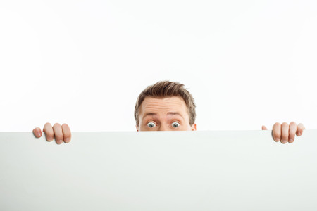Cheerful guy is standing behind horizontal empty whiteboard. He is peeping through it with interest. Isolated on background