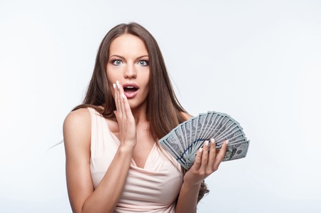 expressing: Pretty girl is holding dollars in her left hand. She is expressing shock. The lady is raising her hand to her mouth. Isolated on background and copy space in left side