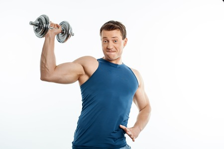 efforts: Handsome sportsman is raising dumbbell up with efforts. He is looking forward with concentration. Isolated on background and copy space in right side