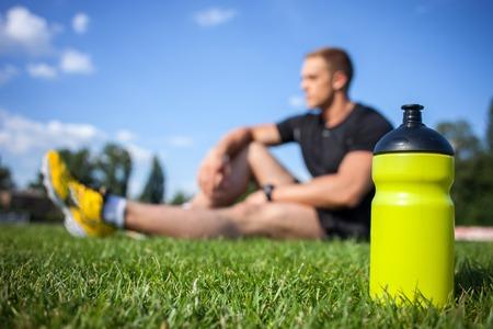 botella: Atleta masculino saludable est� descansando en la hierba. Centrarse en una botella de agua