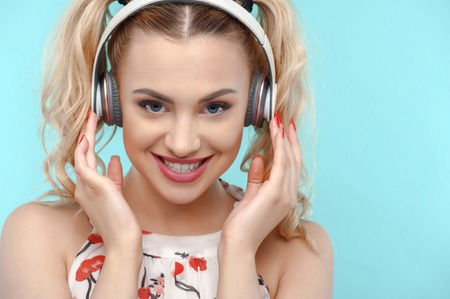 admiration: Beautiful blond girl is smiling and looking at the camera with admiration. She is listening to music from headphones. Isolated on blue background and there is copy space in right side Stock Photo