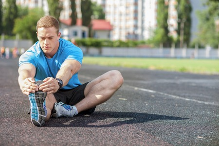 man looking up: Handsome athlete is sitting on the road. He is stretching one leg forward while another leg is bent. He stretches himself with seriousness. There is copy space in right side Stock Photo