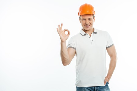 builder: Attractive builder is showing okay sign with happiness. He is smiling and looking forward with joy. Isolated on background and copy space in left side