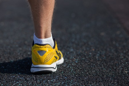 tenseness: Close up of male leg in sneaker. The sportsman is ready to run. There is copy space in right side Stock Photo