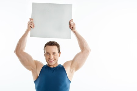 quadrant: Attractive man is raising empty quadrant over his head. He is smiling with joy. Isolated on background and copy space in right side Stock Photo