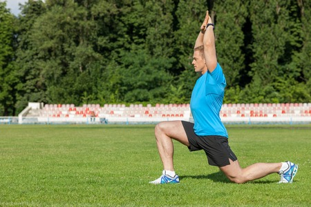 seriousness: Handsome athlete is kneeing and raising his hands up. He is stretching himself. The man is looking forward with seriousness. There is copy space in left side