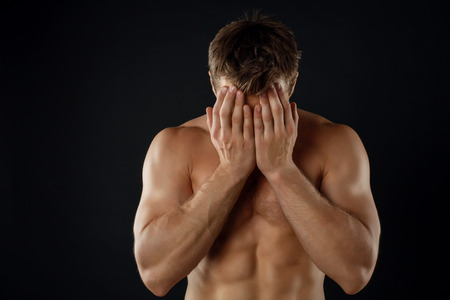 naked black men: Handsome sportsman is covering his face with his palms shamely. His torso is naked. Isolated on black background and there is copy space in left side Stock Photo