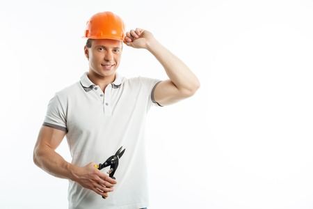 journeyman technician: Handsome builder with helmet on his head is holding shears for cutting metal. He is touching his helmet with his hand. The man is smiling. Isolated on background and copy space in right side