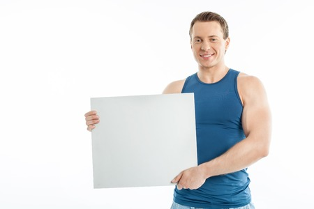 quadrant: Attractive man is holding white quadrant with happiness. He is smiling proudly. Isolated on background and copy space in left side