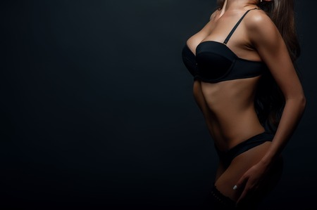 black sex: Close up of waist of beautiful girl showing her black underwear. She is posing confidently. Isolated on black background and there is copy space in left side Stock Photo