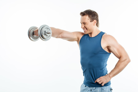 efforts: Attractive athlete is raising dumbbell up with efforts. He is looking at it and smiling. Isolated on background