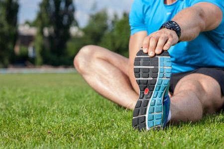 close   up: Close up of legs and torso of fit sportsman sitting on grass. He is stretching his left hand and doing warm-up.  There is copy space in left side