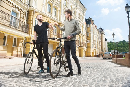 liking: Handsome hipster guys are riding bicycles. Their fists meet as sign of their friendship. The are smiling and liking at each other