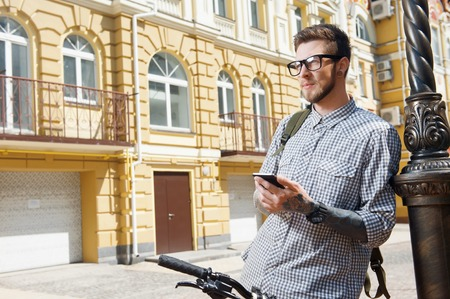 text cool: Handsome young hipster guy is standing near bicycle. He is holding mobile phone and looking seriously and thoughtfully aside. He has backpack on his shoulder