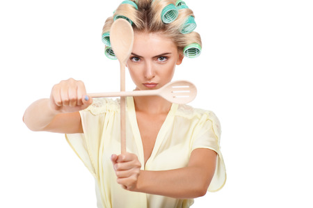 stereotypical housewife: Beautiful housewife with curlers in hair closed two wood spoons protectively. She is looking at the camera with seriousness. Isolated on background and copy space in right side Stock Photo