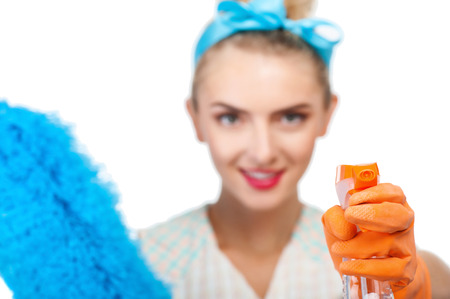 charlady: Pretty woman is directing a bottle of spray at camera. She is holding duster in another hand and smiling. Focus on spray. Isolated on background Stock Photo