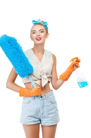 charlady: Beautiful housewife is holding brush against dust and cleaning spray. She is smiling and looking forward with happiness. Isolated on background