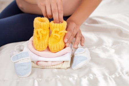 childlike: Close-up of female hands touching baby shoes with love. She is sitting on a bed near other small childlike clothing