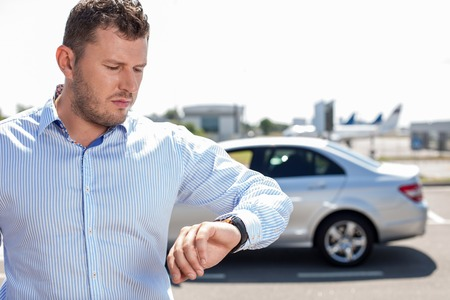 clothes organizer: Cheerful business is looking at his watch nervously. His flight is delayed. He is standing near his car Stock Photo
