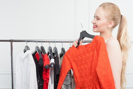 clothing rack: Attractive blond woman wants to try on a new red dress in boutique. She is holding it and smiling