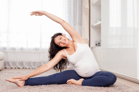 Pretty expectant mother is exercising in her room. She is sitting on floor and stretching her arms aside. The lady is smiling and looking at the camera with joy