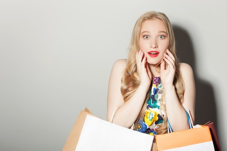 with bag: Cheerful blond girl is expressing shock about sales. She wants to buy everything. She has already many packets. Isolated on background and copy space in left side