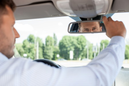 Handsome man is sitting at steering wheel. He is looking at mirror with attention and adjusting it
