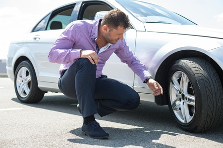 seriousness: Cheerful young businessman has problems with the wheel of his car. He is kneeing and looking at it with seriousness