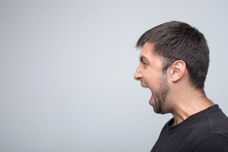 amok: Angry man is evincing his aggression. He is standing in profile and shouting. Isolated on grey background and copy space in left side Stock Photo