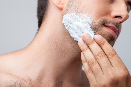 hair treatment: Close up of face of man applying foam on his chin with concentration. Isolated on grey background Stock Photo