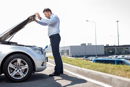 ハンサムな男は、深刻さとボンネットを見ています。彼の車でいくつかの問題があります。右側のスペースをコピーします。 写真素材
