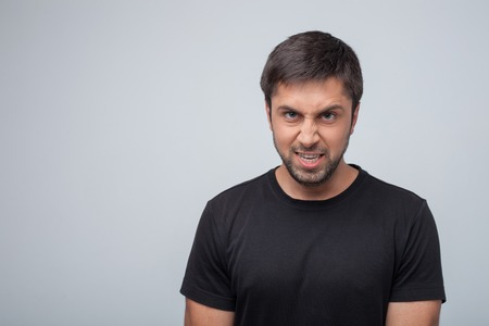 dangerously: Frustrated violent guy is expressing his anger. He is showing his teeth dangerously. Isolated on grey background and copy space in left side Stock Photo