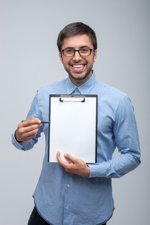 caucasian appearance: Cheerful man with Caucasian appearance is showing a folder with papers. He is directing a pen to it. The man is smiling with happiness. Isolated on grey background