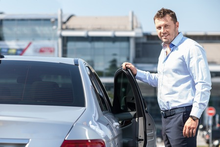 Cheerful man is opening door of his car. He is proposing his business partner to have a sit. He is smiling and looking forward with joy Stock Photo