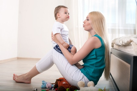 parents and baby: Cheerful mother is teaching her male toddler to talk. She is holding him and sitting on flooring. The mom is looking at her child with love