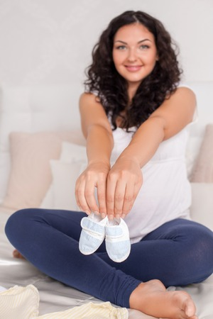 expectant: Beautiful expectant mother is showing baby shoes to camera. She is smiling with joy. The lady is sitting on her bed. Focus on shoes