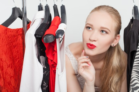 clothing rack: Cute blond girl wants to buy an elegant dress. She is looking at one from the rack and sending kiss to it