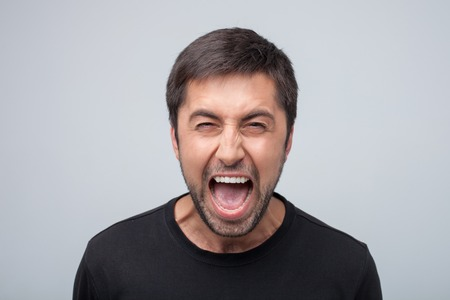 threatens: Displeased aggressive guy is looking at the camera with threatens. He is shouting with frustration and danger. Isolated on grey background