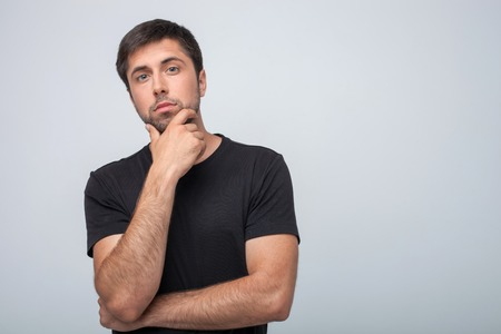 seriousness: Attractive man is looking at the camera pensively. He is thinking about his future. The man is touching his chin with seriousness. Isolated on grey background and copy space in right side