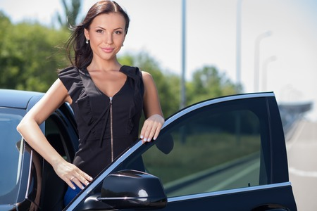 sit down: Beautiful businesswoman is opening door of her car. She is preparing to sit down. The girl is smiling and posing with pride Stock Photo