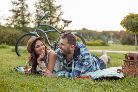 lovers embracing: Pretty loving couple is dating in the nature. They are lying on the cover and embracing. The lovers are drinking wine and smiling. They are looking at each other flirtingly
