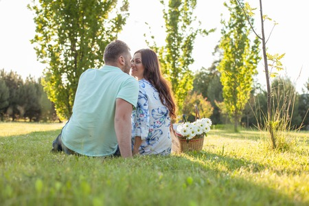 touching noses: Cute loving couple is sitting on grass. They are looking at each other with love and smiling. They are touching their noses together gently. Focus on their back and copy space in right side Stock Photo