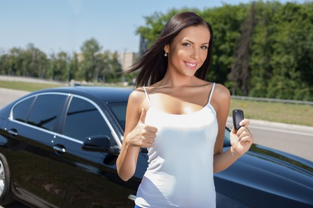 Cheerful girl is giving thumbs up and smiling. She is standing near her new car and holding the showing a key of it. The lady is looking at the camera with happiness