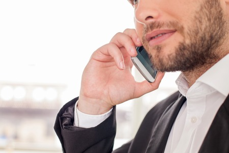 close   up: Close up of attractive man talking on the telephone with his business partner. He is serious an self-confident Stock Photo