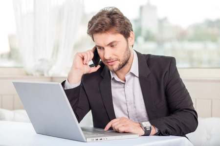 telephone: Handsome businessman is sitting at the table in restaurant and talking on the phone. He is looking at his notebook with concentration