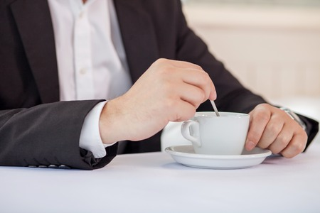 enjoyment: Close up of hands of man drinking coffee. He is sitting and the table in suit