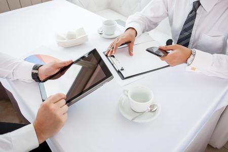 empresario: Cerca de las manos de dos hombres de negocios sentado en la mesa en el restaurante. Ellos están haciendo su trabajo. Un hombre es la celebración de un ordenador portátil. Otro hombre de negocios está escribiendo las ideas principales y la celebración de teléfono Foto de archivo