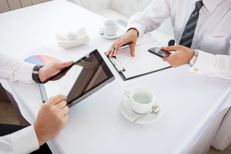 Close up of hands of two businessmen sitting at the table in restaurant. They are doing their work. One man is holding a laptop. Another businessman is writing down main ideas and holding phone